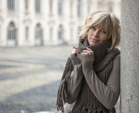 Pretty young blonde woman outdoors, wearing wool scarf and sweater Royalty Free Stock Images