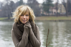 Pretty young blonde woman outdoors, wearing wool scarf and sweater Royalty Free Stock Photos