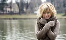 Pretty young blonde woman outdoors, wearing wool scarf and sweater Royalty Free Stock Photography