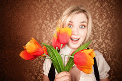 Pretty young blonde woman with plastic flowers Royalty Free Stock Photos