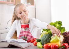 Woman reading recipe book. Pretty young blonde woman reading recipe book and preparing vegetables for lunch. Bright kitchen in background Royalty Free Stock Photography