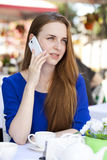 Pretty young blonde woman sitting in the cafe and calling by pho Stock Photos