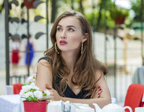 Pretty young blonde woman sitting in the cafe Stock Photography