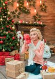 Young woman opening present box in interior New Year studio stock image