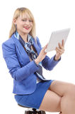 Pretty young blonde woman with a tablet, sitting on a stool Royalty Free Stock Images