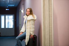 Pretty Young Blonde Woman Traveling Wearing a coat, jeans pulling a suit case royalty free stock image
