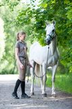 Pretty young blondy teenage girl with her favorite white horse. Pretty young blondy cheerful teenage girl equestrian standing with her favorite white horse Stock Photo