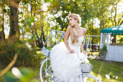 Pretty young bride with bike Stock Photo