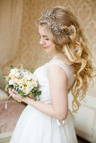 Pretty young Bride. Boudoir morning of the bride. Looks on her bouquet royalty free stock photo