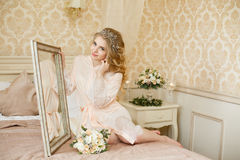 Pretty young Bride. Boudoir morning of the bride. Sit on the bed near the mirror stock image