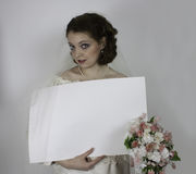 Pretty young bride holds blank sign Stock Image