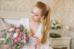 Pretty young Bride`s wedding morning. Pretty young Bride. blonde-haired woman with wedding hair-style with a long tail. Boudoir morning of the bride. Looking on Royalty Free Stock Images