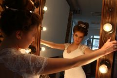 Pretty young bride in white dress looks in mirror. With lamps in studio royalty free stock photos
