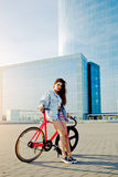 Pretty young brown haired woman standing with her modern pink bicycle in city Stock Images