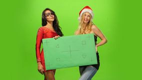 A pretty young brunette and blond womans in Santa stock video footage