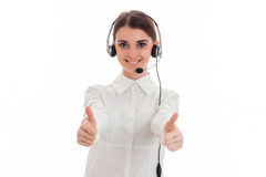 Pretty young brunette call office worker woman with headphones and microphone smiling and showing thumbs up on camera Stock Photo