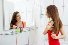 Pretty young brunette combs hair in a bathroom Stock Photography