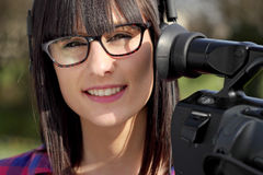 Pretty young brunette girl with a professional camcorder Stock Photography