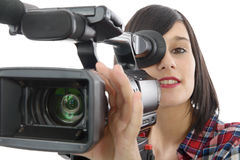Pretty young brunette girl with a professional camcorder, on whi Royalty Free Stock Photo