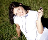 Pretty young brunette girl show pink music player. Stock Image