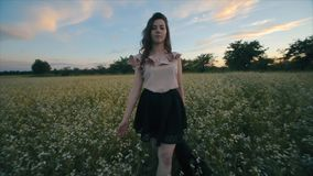 Pretty young brunette girl with a wavy hair in black skirt walks in a flower field. Rear view. Slow motion stock video