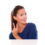 Pretty young brunette making a victory sign Stock Photos