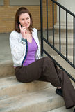 Pretty Young Brunette Model Talking On Cell Phone. While sitting on concrete steps outdoors Royalty Free Stock Images