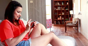 Pretty young brunette relaxing on sofa using smartphone. At home in living room stock video