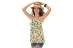 Pretty young brunette in sarafant with floral pattern and straw hat looking and smiling on camera isolated on white Royalty Free Stock Photo