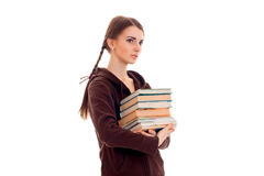 Pretty young brunette student girl with a lot of books in hands isolated on white background Stock Photo