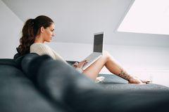Pretty young brunette using laptop at home Royalty Free Stock Photo