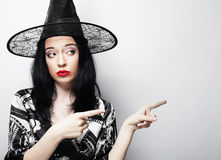 Pretty young brunette witch with black hat Royalty Free Stock Photo
