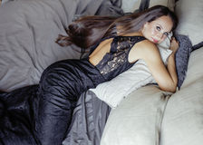 Pretty young brunette woman in bedroom interior smiling, shades of grey, seduction concept Royalty Free Stock Images