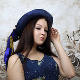 Pretty young brunette woman in blue hat portrait Stock Photography
