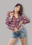 Pretty young brunette woman with a checkered shirt on grey backg Stock Photos