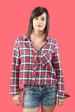 Pretty young brunette woman with a checkered shirt on pink backg Royalty Free Stock Photos