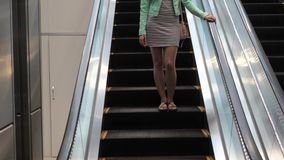 Pretty Young Brunette Woman Coming Down The Escalator. Lovely young brunette woman in a dress with a handbag and a jacket goes down the escalator. She stock video footage