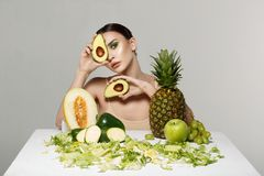 Pretty young brunette woman covering eye with fresh ripe green avocado stock photography