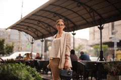 Pretty young brunette woman dressed casual posing outdoor with leather handbag Royalty Free Stock Image