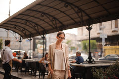Pretty young brunette woman dressed casual posing outdoor with leather handbag Royalty Free Stock Images