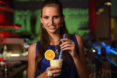 Pretty young brunette woman drinking cocktail in bar. At night Royalty Free Stock Photo