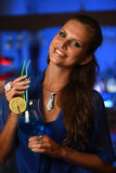 Pretty young brunette woman drinking cocktail in bar. At night Stock Photography