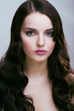 Pretty young brunette woman with hair style like cute doll hairstyle waves, glamorous makeup Royalty Free Stock Photos