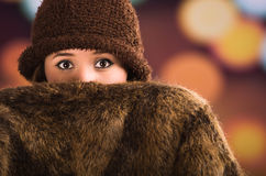 Pretty young brunette woman holding fur style jacket covering half face, brown hat posing with blurry light drops Royalty Free Stock Photos