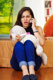 Pretty young brunette woman holding pregnancy home test, talking on phone and looking shocked, teddybear in lap, garden Royalty Free Stock Image