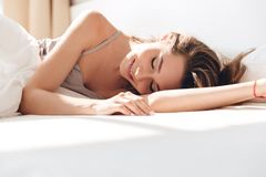 Pretty young woman sleep in bed. Pretty young brunette woman in pajamas sleep in bed in the morning royalty free stock image