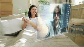 Woman recieves video call on hologram screen stock footage