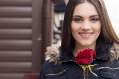 Pretty young brunette woman and red rose. Portrait of beautiful woman with red rose Stock Image