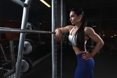 Pretty young brunette woman is relaxing near barbell in dark gym stock photos