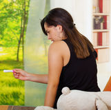 Pretty young brunette woman sittin down while looking at pregnancy home test, back facing camera, bookshelves and garden Stock Photos